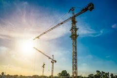 Three construction cranes in a row, against sunlight with beauti Royalty Free Stock Images