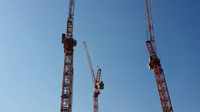 Three construction cranes that stand side by side against the blue cloudless sky. The view from the pleasure boat stock video