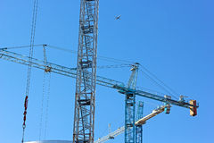 Three construction cranes work a side by side. Royalty Free Stock Image