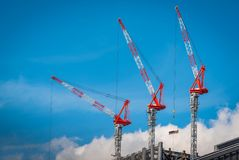 Three construction tower cranes operation at a construction site Royalty Free Stock Image
