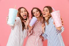 Three content women with good mood in colorful striped pyjamas s. Miling and drinking cold soda from paper cups during fun slumber party isolated over pink Royalty Free Stock Photography