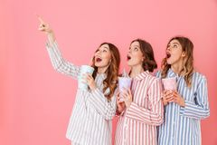 Three content women with good mood in striped pyjamas smiling an. D looking upward on copyspace while drinking soda from paper cups at home isolated over pink Royalty Free Stock Photo