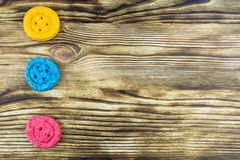 Three  cookies in the form of buttons of different colors lie on. Three  round cookies  in the form of buttons: yellow, blue, pink,  lie on a wooden background stock photography