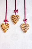 Three cookies in the shape of heart with little bows of silk ribbon Royalty Free Stock Images