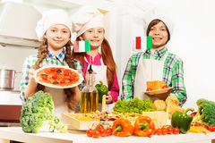 Three cooks with traditional Italian food products Stock Photography