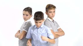 Three cool brothers at white background. Cool gang of three boys at white background. Boys from both sides looks seriously at camera and holds their hands stock video