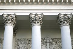 Three corinthian columns supporting the cornice of the church. White bulding in greek style royalty free stock photo