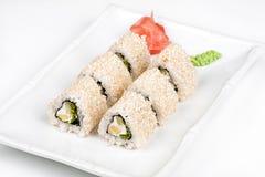 Three-cornered sushi roll with fish, cucumber and green salad. Three-cornered sushi roll with fish, cucumber and green salad on the plate Royalty Free Stock Image