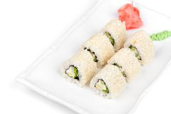 Three-cornered sushi roll with fish, cucumber and. Green salad on the plate Royalty Free Stock Image