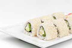 Three-cornered sushi roll with fish, cucumber and. Green salad on the plate Royalty Free Stock Images