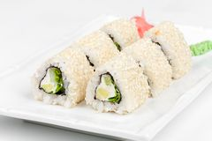Three-cornered sushi roll with fish, cucumber and. Green salad on the plate Stock Photo