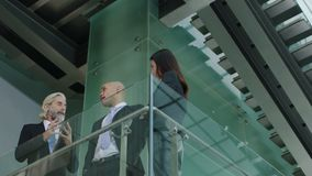 Three corporate business people standing and talking in modern office building. Three corporate executives standing on second floor of a modern glass and steel