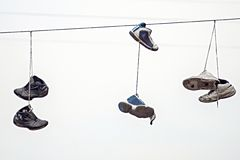 Three couples old sneakers on wires Stock Photos