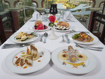 Three course meals in an a la carte restaurant. Two settings of three course meals in an a la carte restaurant with window view stock photo