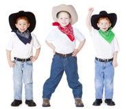 Three cowboys. Three boys dressed up as cowboys in studio stock image