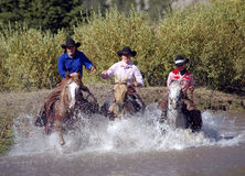 Three Cowgirls Crossing Pond. Splashing water royalty free stock image