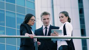 Three coworkers standing on the terrace of office building and talking about their working day and meetings. Three coworkers standing on the terrace of office stock video footage