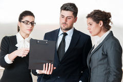 Three coworkers talking over a clip board Royalty Free Stock Photography