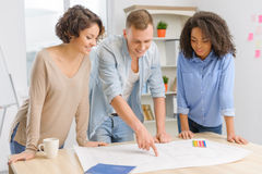 Three coworkers are working with construction. Fruitful work. Three young intelligent colleagues are standing beside the common table and actively discussing Royalty Free Stock Photography
