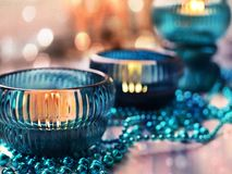 Three cozy lighted candles in turquoise candlesticks with Christmas garland in warm colors with bokeh effect stock photo