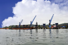 Three crane unloading coal from barge to hopper Royalty Free Stock Images