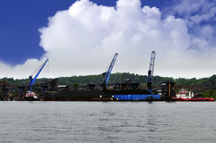 Three crane unloading coal from two barge Stock Photo