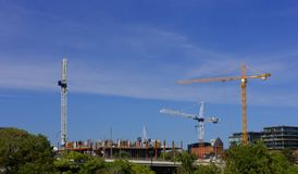 Three cranes on construction site blue sky clouds royalty free stock images