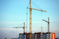 , three cranes on top of high-rise building Royalty Free Stock Photos