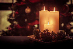 Three cream candles burn before festive tree Royalty Free Stock Photography