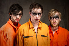 Three criminals in orange uniforms Stock Images