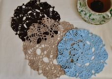 Three crochet doily of different colors and cup of tea. Three crochet doily of different colors and  cup of black tea on the  table Royalty Free Stock Photography