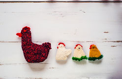 Three crocheted Easter chickens and knitted hen,white wooden background. Three colorful crocheted Easter chickens and knitted hen against old white wooden royalty free stock photography