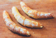Three croissant on a wooden cutting board close-up Royalty Free Stock Photo