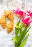 Three croissants and bright pink tulips on lace tablecloth Royalty Free Stock Photo