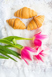 Three croissants and bright pink tulips on lace tablecloth Stock Images