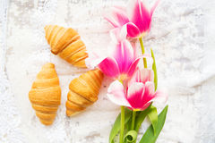 Three croissants and bright pink tulips on lace tablecloth, close-up Royalty Free Stock Photos
