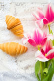 Three croissants and bright pink tulips on lace tablecloth, close-up Royalty Free Stock Photo