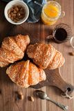 Three croissants with cheese crust lie on a wooden board on a wooden table next to tea, almonds, apricot jam and spoon Royalty Free Stock Images