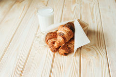 Three croissants with chocolate and milk on wood table Royalty Free Stock Image