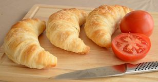 Three Croissants, Knife and Tomatoes. Stock Image