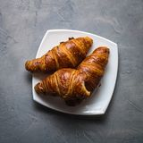 Three croissants and one bitten in a white saucer on a gray concrete background. Top view Stock Photo