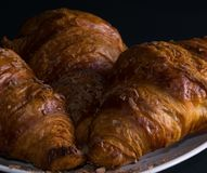 Three croissants on a white plate, dark background, front view. With chocolate chips and crumbs. Ready for breakfast. Close up Stock Images
