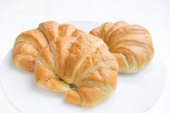 Three croissants on white plate. Stock Images