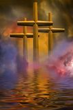 Three crosses. Three golden crosses rising out of water surrounded by story clouds.  Vivid colors Royalty Free Stock Image