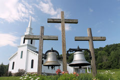 Three crosses in front of church. Two large bells hanging from three wooden crosses in front of a newly restored historic church in Morrisville, New York Stock Image