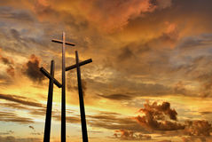 Three crosses on a hill over bright sunset Stock Photo
