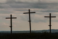 Three Wooden Crosses Stand Against A Dark Ominous Sky. Three crosses in a North Georgia field stand against an ominous sky Stock Images