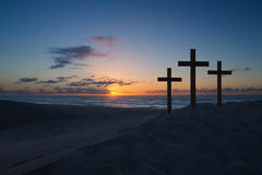 Three crosses on sand dune next to the ocean with a cloudy sunri Stock Images