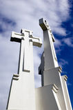 Three crosses on sky background, monument. There are three white crosses on cloudy sky background Royalty Free Stock Photos