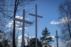 Three crosses in trees against a cloudy blue sky royalty free stock photography
